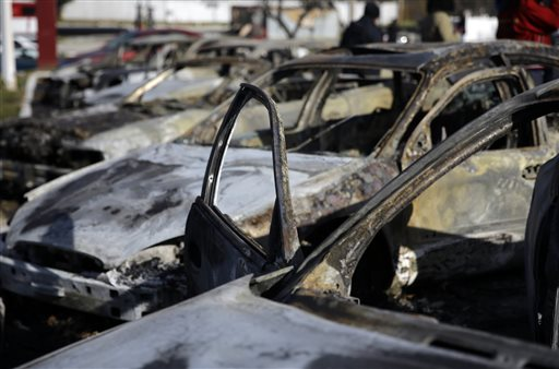 A row of burned cars sit on the lot of a used car dealer Tuesday, Nov. 25, 2014, in Dellwood, Mo. The cars are one example of property damage caused by rioters after a grand jury decided not to indict a Ferguson police officer in the shooting death of Michael Brown. (AP Photo/Jeff Roberson)