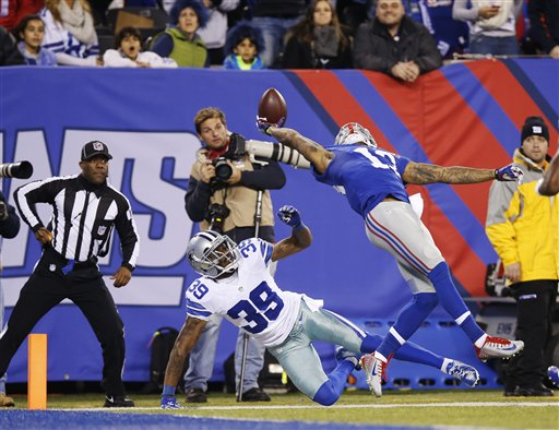 New York Giants wide receiver Odell Beckham Jr. (13) makes a one-handed catch for a touchdown against Dallas Cowboys cornerback Brandon Carr (39) in the second quarter of an NFL football game, Sunday, Nov. 23, 2014, in East Rutherford, N.J.  (AP Photo/Kathy Willens)