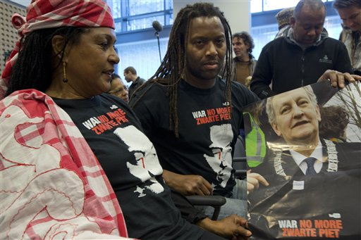 """People wearing T-shirts reading """"World Against Racism, No More Black Pete"""" and holding a poster with a picture of Amsterdam mayor Eberhard van der Laan attend the ruling over a complaint that the city of Amsterdam had no right to authorize a parade with Black Pete because he is a negative stereotype of black people, at the highest Dutch administrative in The Hague, Netherlands, Wednesday, Nov. 12, 2014. The court declined to wade into the increasingly acrimonious national debate around Black Pete, the black-faced sidekick to the Dutch equivalent of Santa Claus, and ruled that the city of Amsterdam was right to grant a permit for parade with Black Petes. (AP Photo/Peter Dejong)"""