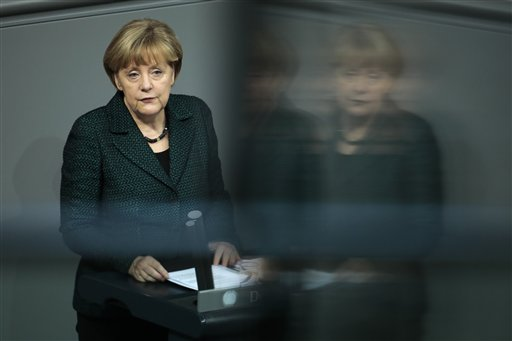 German Chancellor Angela Merkel reflects in a glass window of the visitors tribune as she delivers her speech on the second day of a four days debate of a debt free national budget for 2015 at the parliament Bundestag in Berlin, Germany, Wednesday, Nov. 26, 2014.  (AP Photo/Markus Schreiber)