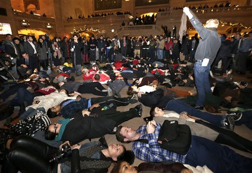 People lie on the ground at Grand Central Terminal after it was announced that the New York City police officer involved in the death of Eric Garner is not being indicted, Wednesday, Dec. 3, 2014, in New York. A grand jury cleared the white New York City police officer Wednesday in the videotaped chokehold death of Garner, an unarmed black man, who had been stopped on suspicion of selling loose, untaxed cigarettes, a lawyer for the victim's family said. A video shot by an onlooker and widely viewed on the Internet showed the 43-year-old Garner telling a group of police officers to leave him alone as they tried to arrest him. The city medical examiner ruled Garner's death a homicide and found that a chokehold contributed to it. (AP Photo/Julio Cortez)