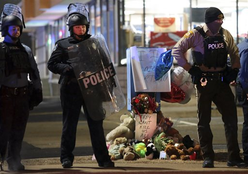 Police guard the entrance to a gas station in front of a memorial to Antonio Martin on Wednesday, Dec. 24, 2014, in Berkeley, Mo. The mayor of the St. Louis suburb of Berkeley urged calm Wednesday after a white police officer killed the black 18-year-old who police said pointed a gun at him, reigniting tensions that have lingered since the death of Michael Brown in neighboring Ferguson. (AP Photo/St. Louis Post-Dispatch, Robert Cohen)