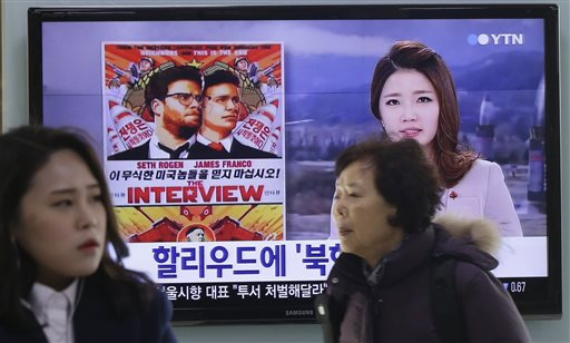 "In this Monday, Dec. 22, 2014, file photo, people walk past a TV screen showing a poster of Sony Picture's ""The Interview"" in a news report,  at the Seoul Railway Station in Seoul, South Korea. A South Korean activist said Wednesday, Dec. 31, 2014, that he will launch balloons carrying DVDs of Sony's ""The Interview"" toward North Korea to try to break down a personality cult built around the country's leader Kim Jong Un. (AP Photo/Ahn Young-joon, File)"
