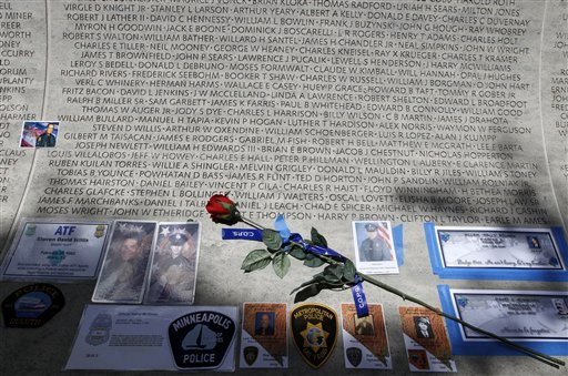 In this May 13, 2013 file photo, a rose is placed at the wall with the names of fallen police officers at the National Law Enforcement Officers Memorial in Washington during the National Police Week. The number of law enforcement officers killed by firearms in the U.S. jumped by 56 percent this year and included 15 ambush assaults, according to a report released Tuesday. The annual report by the nonprofit National Law Enforcement Officers Memorial Fund found that 50 officers were killed by guns this year, compared to 32 in 2013. (AP Photo/Jose Luis Magana, File)