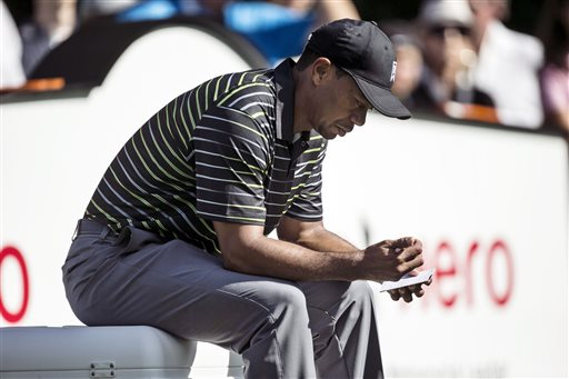 Tiger Woods looks over his scorecard as he waits to tee off on the seventh hole during the first round of the Hero World Challenge golf tournament on Thursday, Dec. 4, 2014, in Windermere, Fla. (AP Photo/Willie J. Allen Jr.)