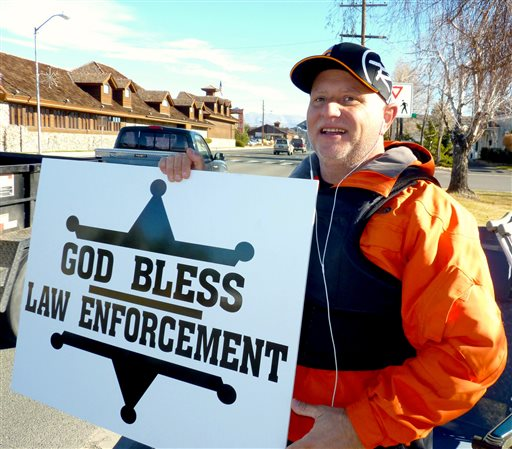 "In this Dec. 22, 2014 photo, passing motorists honk as retired Douglas County sheriff's deputy John Munk of Gardnerville, Nev., holds a sign showing his support for law enforcement, in front of the Minden Post Office south of Carson City. ""It's disheartening how people are treating law enforcement across the country,'' said Munk, who retired in 2012 after more than 20 years on the force. (AP Photo/The Record Courier, Kurt Hildebrand)"