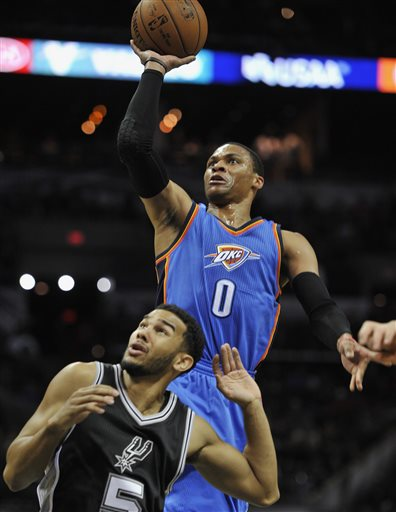 Oklahoma City Thunder guard Russell Westbrook, right, shoots over San Antonio Spurs guard Cory Joseph during the first half an NBA basketball game, Dec. 25, 2014, in San Antonio. (AP Photo/Darren Abate)