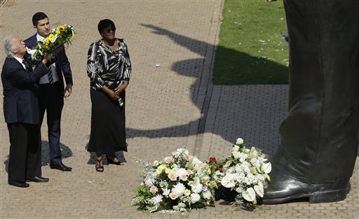 George Bizos, left, human rights lawyer who worked for the late former President Nelson Mandela, accompanied by unidentified officials, looks up before placing a wreath to the 9 meters (30 feet) tall bronze statue of Mandela outside Union Buildings in Pretoria, South Africa, Wednesday, Dec. 5, 2014, on the first anniversary of Mandela's death. Events are to be held around the country for the former statesman who died last year at the age of 95.  (AP Photo/Themba Hadebe)