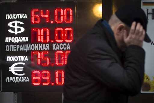 In this Tuesday, Dec. 16, 2014 file photo, a man walks by a sign advertising currencies of an exchange office in Moscow, Russia. Russia has been badly affected by the slide in oil prices in 2014 - the ruble has plunged  despite big increases in interest rates as much of Russia's economy is based on energy. Sanctions on the country for its alleged involvement in the crisis in Ukraine haven't helped the economy either, which appears headed for recession. (AP Photo/Alexander Zemlianichenko, File )