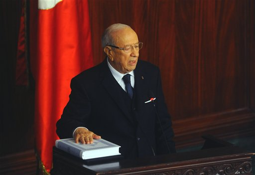 Beji Caid Essebsi, puts his hand on the Quran to be sworn in as new Tunisian President during a ceremony at the National Assembly in Tunis, Tunisia, Wednesday, Dec. 31, 2014. Tunisia's new president pledged a rule of reconciliation and consensus as he took his oath Wednesday before the newly elected parliament to complete the country's democratic transition. The inauguration of Beji Caid Essebsi, an 88-year-old political veteran, comes in a year in which Tunisians wrote a new constitution and elected a new parliament and president, ending a transition kicked off by a revolution. (AP Photo/Hassene Dridi)