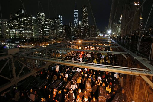Protesters rallying against a grand jury's decision not to indict the police officer involved in the death of Eric Garner carry a collection of mock coffins bearing the names of victims of fatal police encounters as they cross the eastbound traffic lanes of the Brooklyn Bridge, Thursday, Dec. 4, 2014, in New York. A grand jury cleared a white New York City police officer Wednesday in the videotaped chokehold death of Garner, an unarmed black man, who had been stopped on suspicion of selling loose, untaxed cigarettes.  (AP Photo/Jason DeCrow)