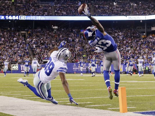 In this Nov. 23, 2014, file photo, New York Giants wide receiver Odell Beckham Jr. (13) makes a one-handed catch for a touchdown against Dallas Cowboys cornerback Brandon Carr (39) in the second quarter of an NFL football game in East Rutherford, N.J. Beckham's acrobatic, one-handed reception during a breakout performance for the Giants in prime time is being trumpeted as the greatest catch of the season. (Julio Cortez, AP)