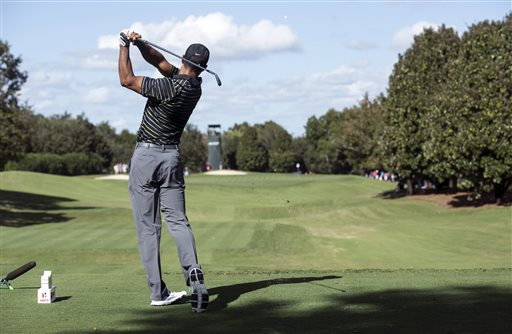 Tiger Woods tees off on the fifth hole during the first round of the Hero World Challenge golf tournament on Thursday, Dec. 4, 2014, in Windermere, Fla. (AP Photo/Willie J. Allen Jr.)