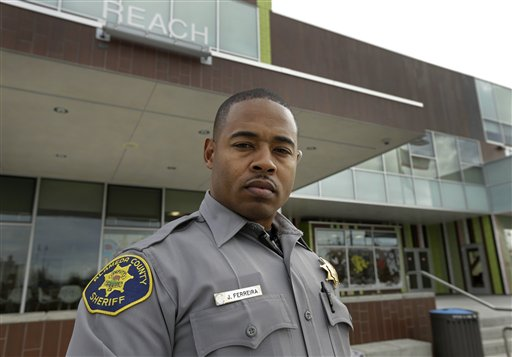 "This photo taken Dec. 8, 2014 shows Alameda County Deputy Sheriff Jorge Ferreira in front of the REACH Crime Prevention unit in San Leandro, Calif. Jorge ""Jinho"" Ferreira feels the tension between being black and carrying a badge every day as a sheriff's deputy in Alameda County, California. ""I feel like you have to prove yourself on every level,"" said Ferreira, 39, who patrols about 30 miles east of San Francisco. ""You have to prove yourself to the black community, you have to prove yourself to all of your co-workers, you have to prove yourself to society."" With the nation roiled by two grand juries' recent refusal to indict white police officers in the deaths of unarmed black men, some black police officers say that as they enforce the law, they also wonder whether the system they're sworn to uphold is stacked against black men. (AP Photo/Ben Margot)"