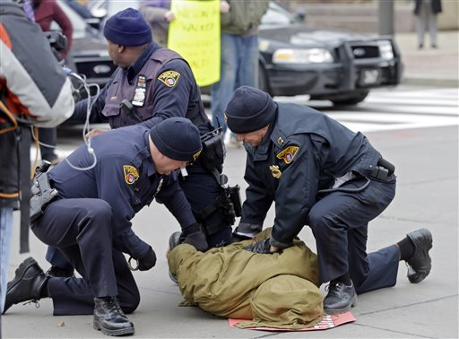 In this Nov. 25, 2014 file photo, police arrest a demonstrator protesting against the shooting of 12-year-old boy Tamir Rice, who was fatally shot by a police officer in Cleveland. The revelation that Cleveland police officials didn't review the checkered history of a police officer who fatally shot a 12-year-old boy highlights what some describe as an unnerving truth about policing -- there's no universal standard for how deeply a department should dig into its recruits' pasts. (AP Photo/Mark Duncan, file)