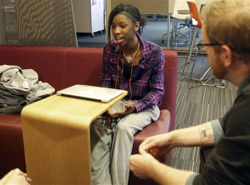 English teacher Tom Rademacher, right, listens as junior Kierra Murray talks about Ferguson, Tuesday, Dec. 2, 2014, at Fair School in Minneapolis. Knowing that the grand jury decision not to indict a white officer who shot and killed a black teen in Ferguson, Mo., would be on the minds of his students, Rademacher put aside his lesson plans and asked them a question: How did they feel? (AP Photo/Jim Mone)