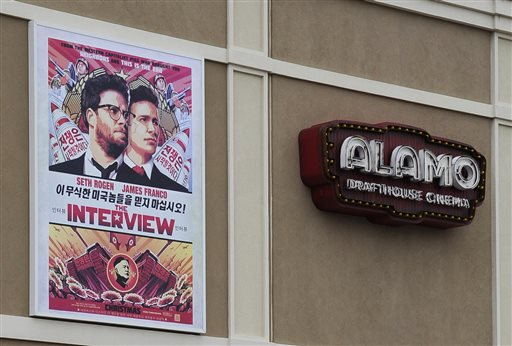 """A large poster advertising the movie The Interview hangs on the back wall of the Alamo Drafthouse Cinema Tuesday, Dec. 23, 2014, in Houston. Sony Pictures Entertainment announced Tuesday a limited theatrical release of """"The Interview"""" beginning Thursday, putting back into the theaters the comedy that prompted an international incident with North Korea and outrage over its cancelled release. (AP Photo/Pat Sullivan)"""