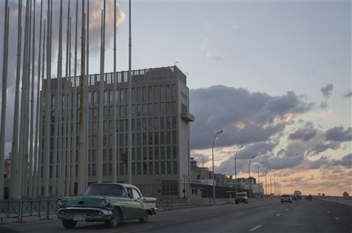 FILE - This Dec. 17, 2014 file photo shows a classic American car driving past the U.S. Interests Section buidling in Havana, Cuba. A half-century after Washington severed relations with Cuba, the seven-story mission is set to become a full-fledged embassy. The U.S. and Cuba announced on Dec. 17, 2014 they are re-establishing full diplomatic relations. (AP Photo/Desmond Boylan, File)