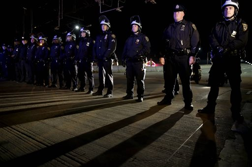 Police officers block protesters from marching up a highway entrance ramp in response to the grand jury's decision in the Eric Garner case in Times Square in New York, Wednesday, Dec. 3, 2014. The grand jury cleared a white New York City police officer Wednesday in the videotaped chokehold death of Garner, an unarmed black man, who had been stopped on suspicion of selling loose, untaxed cigarettes, a lawyer for the victim's family said. (AP Photo/Seth Wenig)