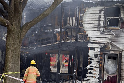 A firefighter stands outside a smoldering house where a small private jet crashed in Gaithersburg, Md., Monday, Dec. 8, 2014. A woman and her two young sons inside the home and three people on the aircraft were killed, authorities said. (AP Photo/Jose Luis Magana)