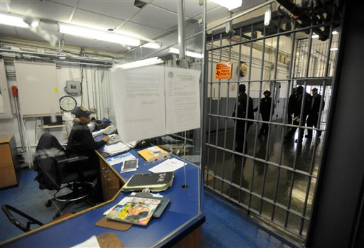 In this Nov. 14, 2013, file photo, a corrections officer works at a security post at the Baltimore City Detention Center in Baltimore. A gang commander who impregnated four guards and ran a sophisticated drug and cellphone smuggling ring inside the center, has revealed information about widespread corruption inside the facility. (AP Photo/Steve Ruark, File)