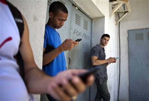 In this April 1, 2014 file photo, students stand outside a building to find an Internet signal for their phones in Havana, Cuba. In programs revealed by the Associated Press in 2014, USAID secretly created a primitive social media program called ZunZuneo, staged a health workshop to recruit activists and infiltrated Cuba's hip-hop community. Those programs were part of a grassroots campaign aimed at undermining the Castro government through the citizenry, rather than directly targeting political leaders. (AP Photo/Ramon Espinosa, File)