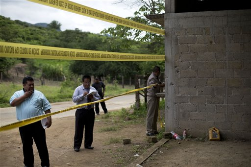 In this July 3, 2014 file photo, state authorities use crime scene tape to seal off an unfinished warehouse that was the site of a shootout between Mexican soldiers and alleged criminals on the outskirts of the village of San Pedro Limon in Mexico state, Mexico. The army killings first came to light with a June 30 press release stating that soldiers on patrol near the town had come under fire and engaged in a fierce shootout that killed 22 gangsters, but left only one soldier wounded--an imbalance that raised questions. (AP Photo/Rebecca Blackwell, File)