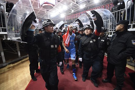 In this photo taken Sunday Nov. 30, 2014, Chinese security guards hold up shield to protect Beijing Ducks' Stephon Marbury during a CBA match between his team and Shanxi Dragons in Taiyuan in northern China's Shanxi province. After a tumultuous career in the NBA, Stephon Marbury says he's found peace in China, thriving on the court with the Beijing Ducks, mentoring young Chinese teammates and becoming one with his adopted home town. Now he has an even bigger goal in mind, to one day coach China''s national team. (AP Photo)
