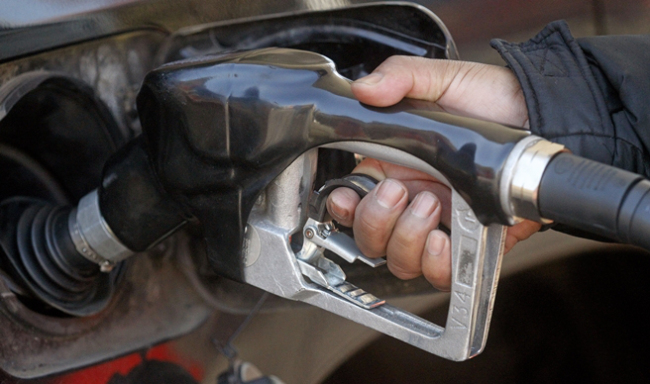 A gas station attendant pumps gas in Portland on March 23, 2012 (AP Photo)