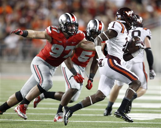 """In this Sept. 6, 2014, file photo, Ohio State lineman Joey Bosa (97) and linebacker Raekwon McMillian (5) chase Virginia Tech receiver Isaiah Ford (1) during an NCAA college football game in Columbus, Ohio. """"Three of the four guys that they play with up front are going to play on Sundays,"""" said Rutgers coach Kyle Flood, whose team was among the many the Buckeyes overwhelmed this year. """"Most teams have one. If you have two you are really good up front. They have three. Bosa headlines the group, but defensive tackles Michael Bennett and Adolphus Washington are also future high-round draft picks. (AP Photo/Paul Vernon, File)"""