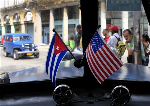 In this March 22, 2013 file photo, miniature flags representing Cuba and the U.S. are displayed on the dash of an American classic car in Havana, Cuba.  The Obama administration is putting a large dent in the U.S. embargo against Cuba as of Friday, significantly loosening restrictions on American trade and investment. The new rules also open up the communist island to greater American travel and allow U.S. citizens to start bringing home small amounts of Cuban cigars after more than a half-century ban. (AP Photo/Franklin Reyes, File)