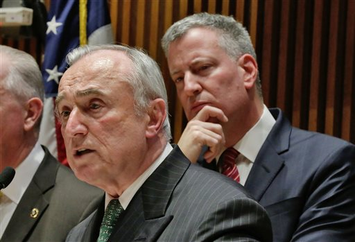 "New York Mayor Bill de Blasio, right, listens as New York City Police Commissioner William Bratton addresses a news conference at New York City Police headquarters, Monday, Jan. 5, 2015. De Blasio says it was ""disrespectful"" that some NYPD officers turned their backs to him during a pair of funerals for slain police officers. (AP Photo/Richard Drew)"