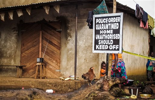 In this Wednesday, Oct. 22, 2014 file photo, a child stands near a sign advising of a quarantined home in an effort to combat the spread of the Ebola virus in Port Loko, Sierra Leone. On Thursday, Jan. 15, 2015, the U.N.'s Ebola chief, Dr. David Nabarro, said at least 50 Ebola hotspots remain in the three hardest-hit West African countries but new cases are declining and the deadly disease will be defeated. In the week ending Jan. 11, WHO said new cases in Sierra Leone declined for a second week to the lowest level since the end of August. (AP Photo/Michael Duff, File)