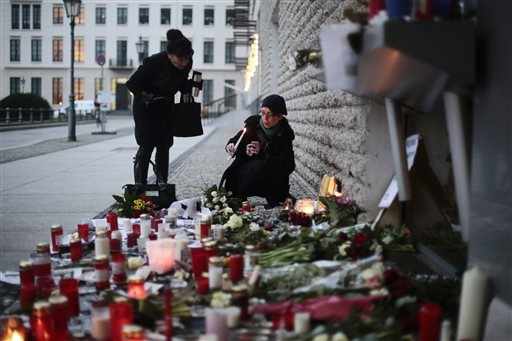 Women light candles to commemorate the victims killed in an attack at the Paris offices of the weekly newspaper Charlie Hebdo, in front of the French Embassy in Berlin, Thursday, Jan. 8, 2015. Masked gunmen stormed the Paris offices of the weekly newspaper that caricatured the Prophet Muhammad, methodically killing 12 people Wednesday, including the editor, before escaping in a car. It was France's deadliest postwar terrorist attack. (AP Photo/Markus Schreiber)