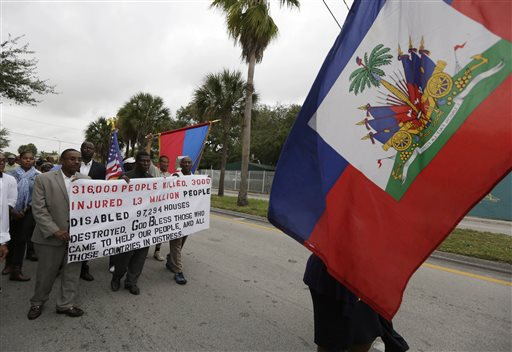 People walk carrying signs and the Haitian flag during a silent march commemorating the fifth anniversary of a devastating earthquake that struck Haiti, Monday, Jan. 12, 2015, in the Little Haiti neighborhood of Miami. The 7.0 magnitude earthquake struck in 2010, and the Haitian government has said more than 300,000 people were killed. The exact toll is unknown because there was no systematic effort to count bodies among the chaos and destruction. (AP Photo/Lynne Sladky)