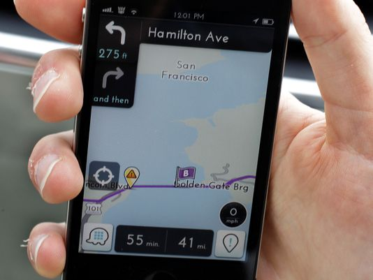 In this March 15 photo, Ben Gleitzman demonstrates a traffic and navigation app called Waze on his Apple iPhone outside of his car in Menlo Park, Calif., showing a map of San Francisco and the Golden Gate Bridge. (Paul Sakuma/AP Photo)