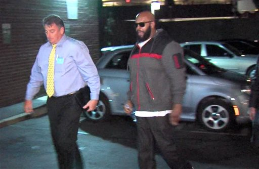 """This image from video shows Death Row Records founder Marion """"Suge"""" Knight, right, walking into the Los Angeles County Sheriffs department early Friday morning Jan. 30, 2015 in connection with a hit-and-run incident that left one man dead and another injured. Man at left is an unidentified police officer. (AP Photo/OnSceneVideo via AP Television)"""