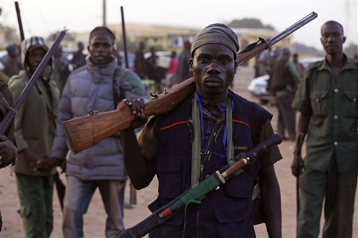In this file photo taken on Wednesday, Nov. 25, 2014, vigilantes and local hunters armed with locally made guns gather before they go on patrol in Yola, Nigeria,  Islamic extremists are rampaging through villages in northeast Nigeria's Adamawa state, killing, burning and looting with no troops deployed to protect civilians, fleeing villagers said Wednesday, Jan. 28, 2015. (AP Photo/Sunday Alamba, File)