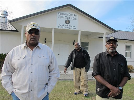 "In this Thursday, Dec. 18, 2014 photo, Alonzo Philmore, left, Harry Campbell, center, and Suwannee County NAACP president Leslie White stand in front of their church in Live Oak, Fla.  In 1952 a wealthy black woman named Ruby McCollum was found guilty by an all-male, white jury for the murder of a prominent white doctor and state senator-elect, Clifford Leroy Adams. A new documentary ""You Belong To Me"" compiles a decade of research and first-time interviews with surviving family members on both sides, and has reopened some old wounds in the small town. (AP Photo/Jason Dearen)"