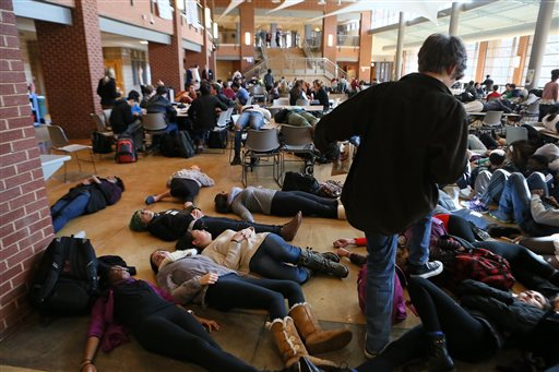 In this Dec. 1, 2014 file photo, students participating in a die lie on the cafeteria floor at Clayton, Mo., High School following a grand jury's decision not to indict a white police officer who killed 18-year-old black Michael Brown. The American Civil Liberties Union filed the lawsuit Monday, Jan. 5, 2015 on behalf of a jury member asking a Missouri court to remove a lifetime order that prevents jurors from discussing the case.  (AP Photo/St. Louis Post-Dispatch,  Cristina Fletes-Boutte, File)