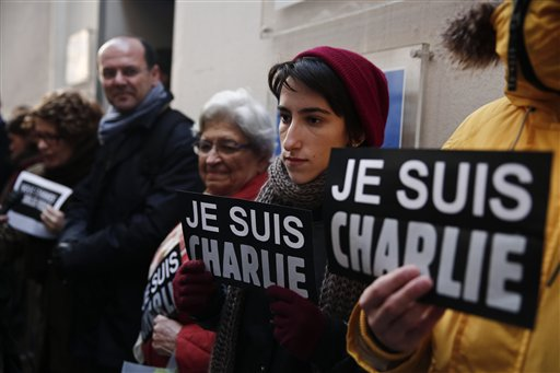 "People hold signs reading ""I am Charlie"" outside the French Institute in Athens on Thursday, Jan.8, 2015. Several hundred people took part in the gathering, as France held a day of mourning for 12 people slain at the Charlie Hebdo offices. Similar protests were planned in several countries worldwide. (AP Photo/Petros Giannakouris)"
