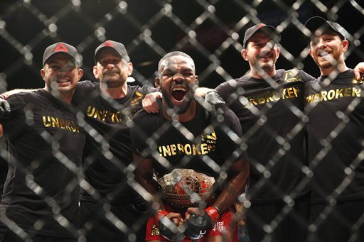Jon Jones celebrates while posing with his corner after defeating Daniel Cormier during their light heavyweight title mixed martial arts bout at UFC 182, Saturday, Jan. 3, 2015, in Las Vegas. (AP Photo/John Locher)