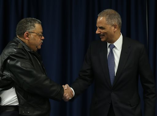 U.S. Attorney General Eric Holder, right, greets  Philadelphia Police Commissioner  Charles A. Ramsey, left, before they participate in the Building Communities of Trust roundtable discussion in Philadelphia on Thursday, Jan. 15, 2015. The roundtable will serve as an opportunity to bring law enforcement, elected officials and members of the community together to discuss next steps that the administration will take to improve relationships between law enforcement and the community, address concerns about violence directed at law enforcement, increase the integrity within our justice system and share best practices for policing. (AP Photo/Philadelphia Inquirer, David Maialetti, Pool)