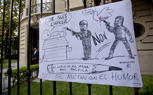 """A cartoon style drawing hangs outside France's embassy that reads in Spanish """"The pencil is the most peaceful weapon, don't mess with humor"""" in solidarity with those killed in an attack at the Paris offices of the weekly newspaper Charlie Hebdo in Buenos Aires, Argentina, Wednesday, Jan. 7, 2015. Masked gunmen stormed the offices of the satirical newspaper that caricatured the Prophet Muhammad, methodically killing 12 people Wednesday, including the editor, before escaping in a car. It was France's deadliest postwar terrorist attack. (AP Photo/Natacha Pisarenko)"""