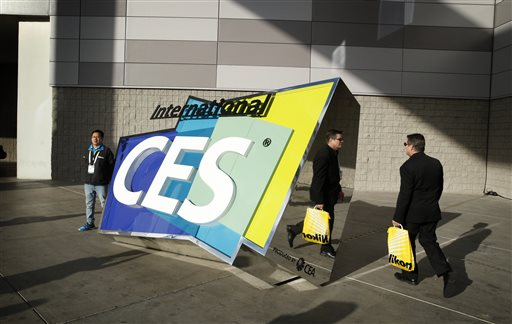 People walk by a sign outside of the International CES, Friday, Jan. 9, 2015, in Las Vegas. (AP Photo/John Locher)