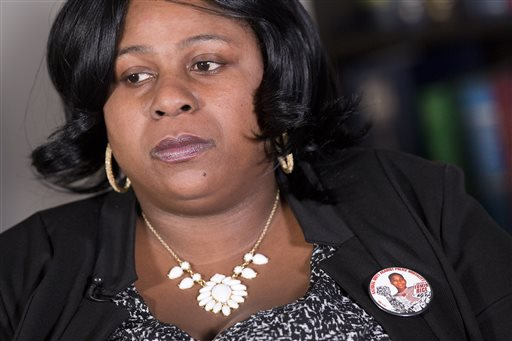 "Samaria Rice, of Cleveland, Ohio, wears a button with her son's photograph during an interview at The Associated Press, Monday, Dec. 15, 2014 in New York. A Cleveland police officer fatally shot 12-year-old Tamir Rice on Nov. 22 as he played with a toy gun outside a recreation center. Rice says her son was never given a chance to follow officers' orders, but she believes the family ""will have justice."" (AP Photo/Mark Lennihan)"