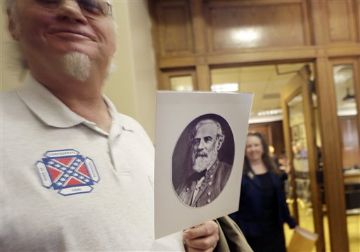 Dewey Spencer, of Judsonia, Ark., holds a portrait of Confederate Gen. Robert E. Lee after a meeting of the House Committee on State Agencies and Governmental Affairs, Wednesday, Jan. 28, 2015, at the State Capitol in Little Rock, Ark. A bid to end Arkansas' practice of commemorating Confederate Gen. Robert E. Lee and civil rights icon Martin Luther King Jr. on the same day has failed before a state House panel. (AP Photo/Danny Johnston)