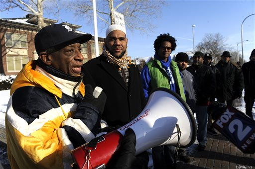 Ron Scott speaks at rally in front of the Grosse Pointe Park city offices in Grosse Pointe Park, Mich. on Wednesday, Jan. 14, 2015.  The protesters want the prosecution of two officers videotaped during the beating of a suspected carjacker in a Detroit neighborhood. A video, taken by a Detroit resident and posted on Facebook, shows what appears to be two white officers taking turns Monday putting their knees in the man's back as he is face down in the snow. The man also is kicked. The Michigan State Police will investigate the officers' actions. (AP Photo/Detroit News, David Coates)  DETROIT FREE PRESS OUT; HUFFINGTON POST OUT
