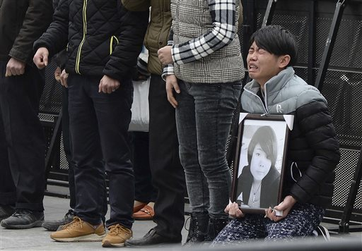 A man holds a portrait of a New Year's Eve stampede victim as he and others mourn over the death of their loved one at the site of the tragic accident in Shanghai, China Tuesday, Jan. 6, 2015. Some wailed and some staggered with grief as the relatives of the 36 people killed in the stampede visited the disaster site Tuesday for seventh-day commemorations that are a revered ritual in China. (AP Photo)