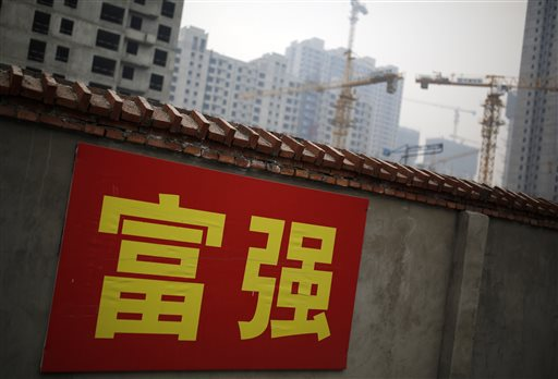 "In this Dec. 9, 2014 file photo, Chinese government propaganda words which read ""Prosperity and Powerful"" are displayed on a wall near a construction site in Beijing, China. China's economic growth slowed to 7.4 percent last year, the weakest expansion in more than two decades. The numbers released Tuesday, Jan. 20, 2014 are still miles ahead of growth rates in major industrialized economies, but represent a sharp decline from double digit growth in previous years. That adds to pressure on the country's communist leaders as they try to prevent a sharper slowdown in 2015 while overhauling the economy.(AP Photo/Andy Wong, FIle)"